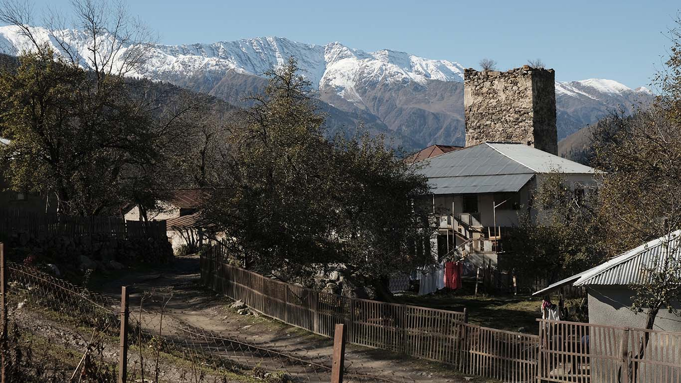 Blick auf einen Ortsteil Lentechis. Das Dorf befindet sich auf der Straße von Zugdidi nach Mestia kurz vor Mestia, dem Verwaltungszentrum Oberswanetiens. Das Bild zeigt einen verfallenden Wehrturm, vor dem sich Wohnhäuser jüngerer Entstehungszeit befinden.